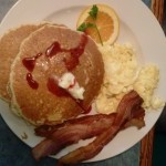 Pancakes with syrup, two eggs and sliced bacon